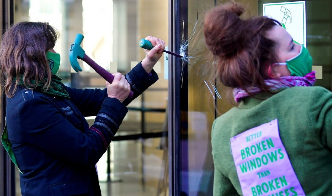 Aktivistler protesto için bankaların camını kırıyor